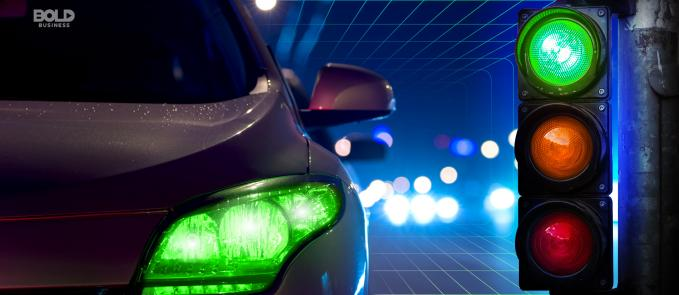 a car's headlight with a lit green bulb and a green-lit stoplight depicting a smart traffic management system in place