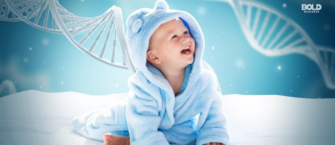 image of a smiling baby in a blue onesie surrounded by magnified DNA strands amid the topic of genetically modified kids