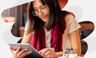 a photo of a young woman wearing glasses reading Wattpad Stories on her smart tablet