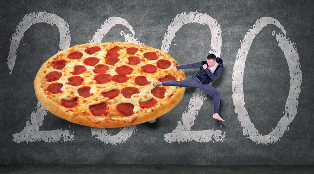a dude sidekicking a giant pizza