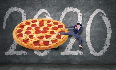 a dude sidekicking a giant pizza