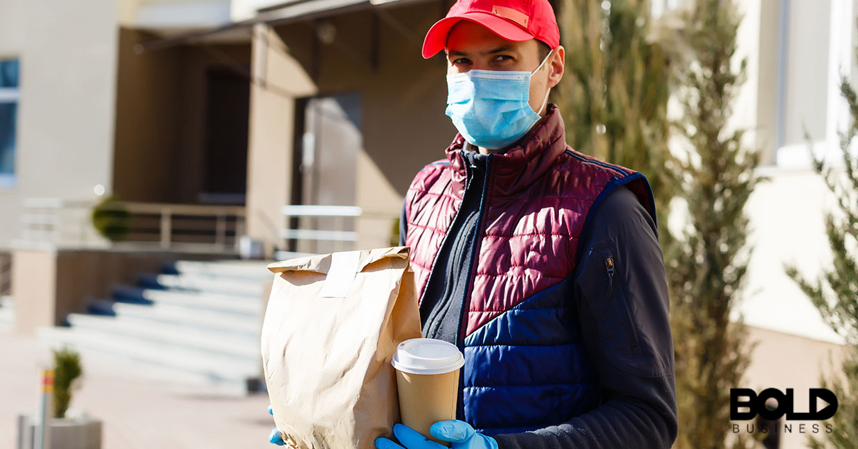Someone delivering coffee and food while wearing a mask and gloves