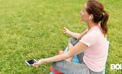 some girl meditating in the park with a mental health app