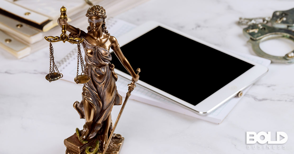 A scales of justice statue and an iPad