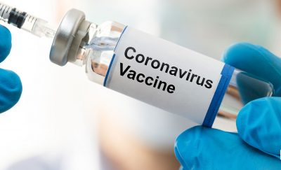 A scientist with a coronavirus vaccine in a vial