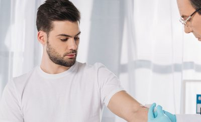 A dude getting his blood taken by a physician