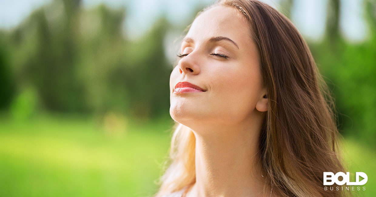 A woman taking a deep breath of fresh air