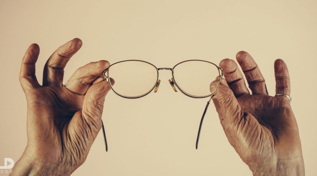 An elderly person holding up a pair of glasses
