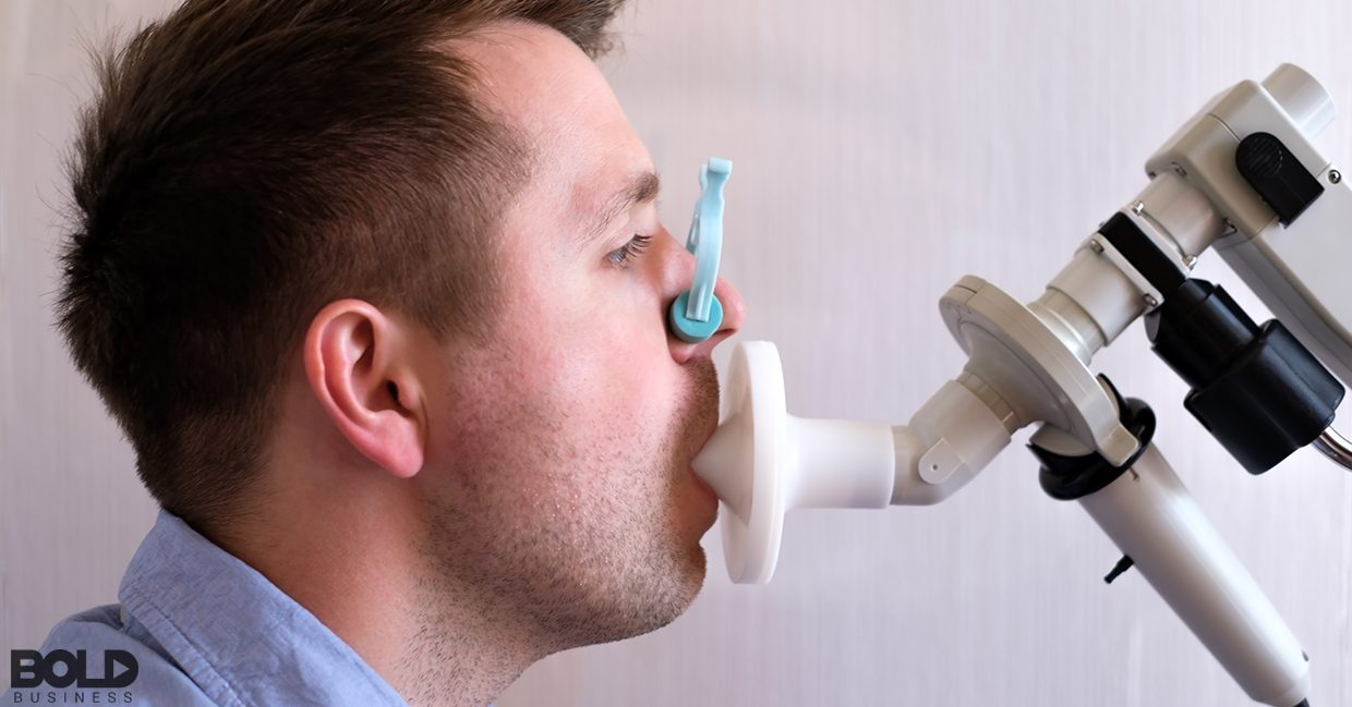 Some dude blowing into some sort of weird medical device