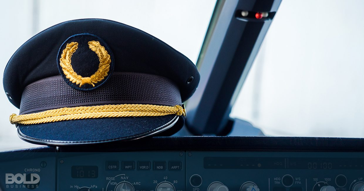 A pilot's cap resting on the dashboard of a cockpit