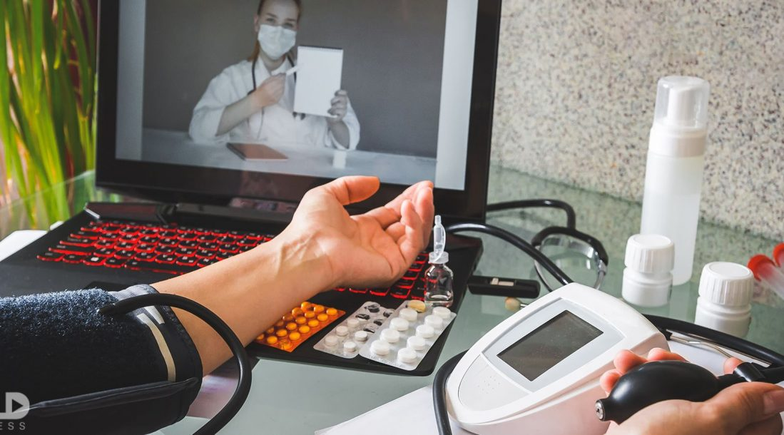 A patient taking their blood pressure while a doctor watches on screen