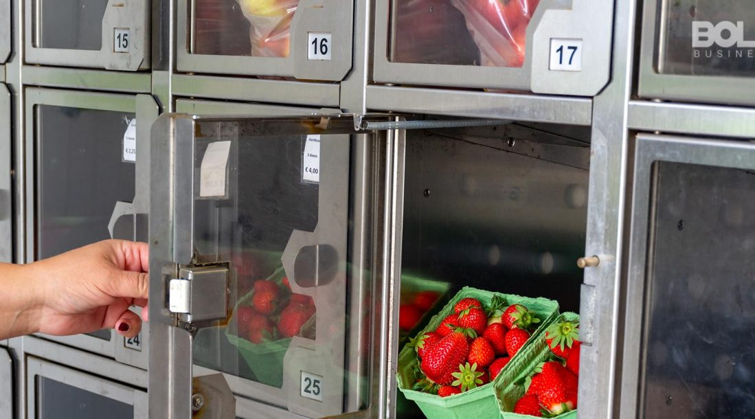 Someone getting some fruit from an automat