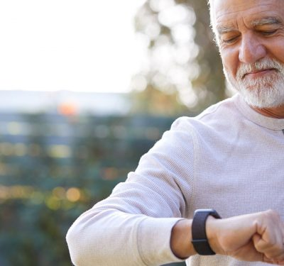 An older dude checking his wearable health monitor