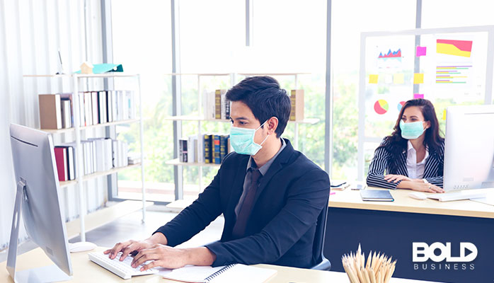 Some people working in an office with masks on