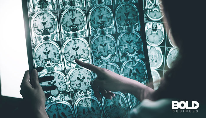 A scan of someone's brain and a doctor pointing at it