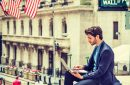 A dude using a trading app while sitting above Wall Street like a gargoyle