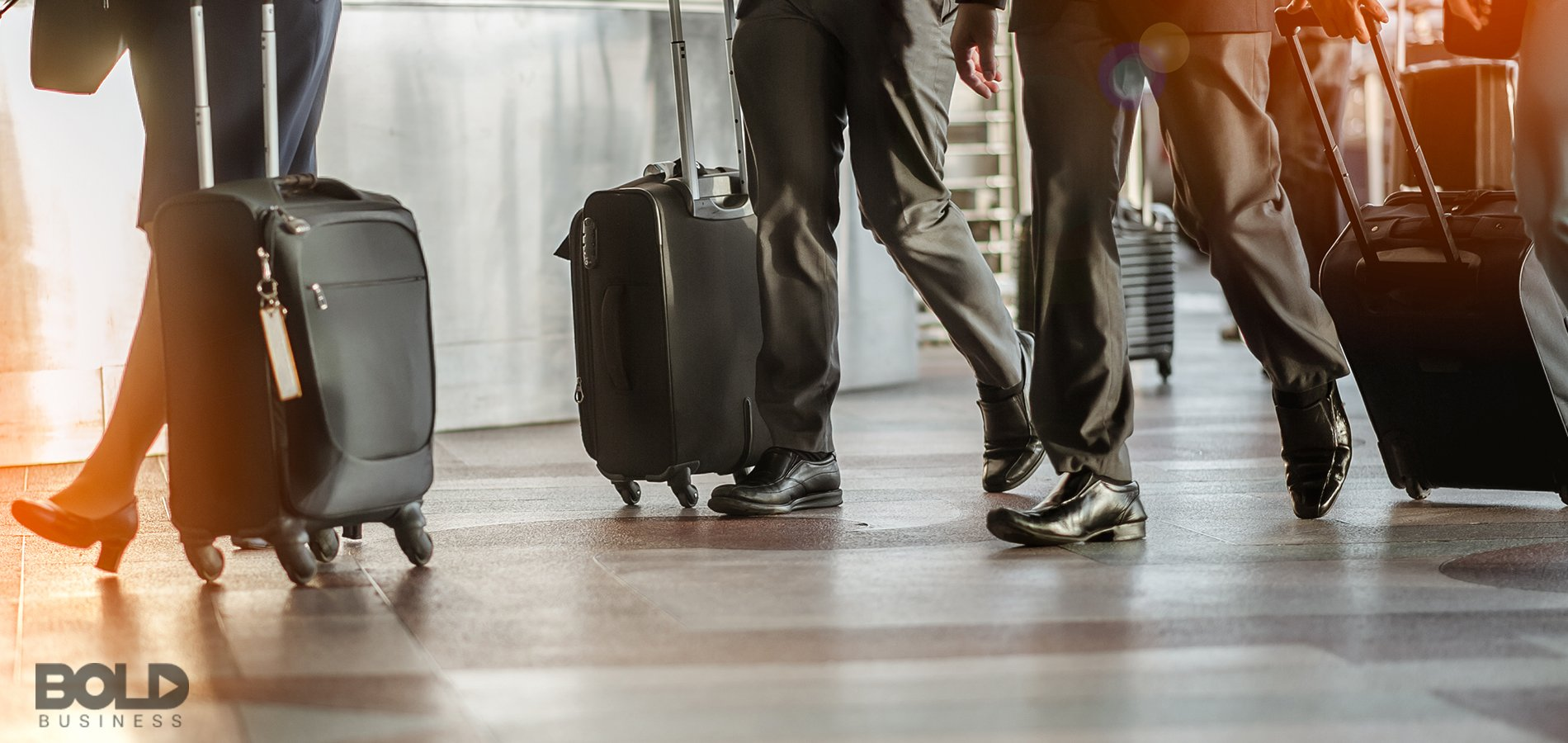 A bunch of business travelers rolling their suitcases along