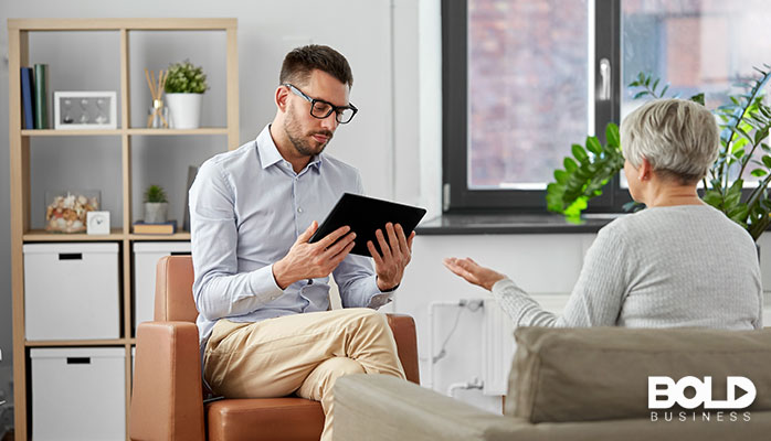 A therapist paying more attention to his tablet than his patient.