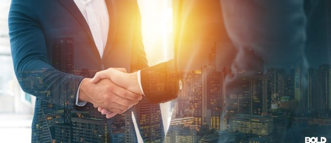 Two businessmen shaking hands before the sun