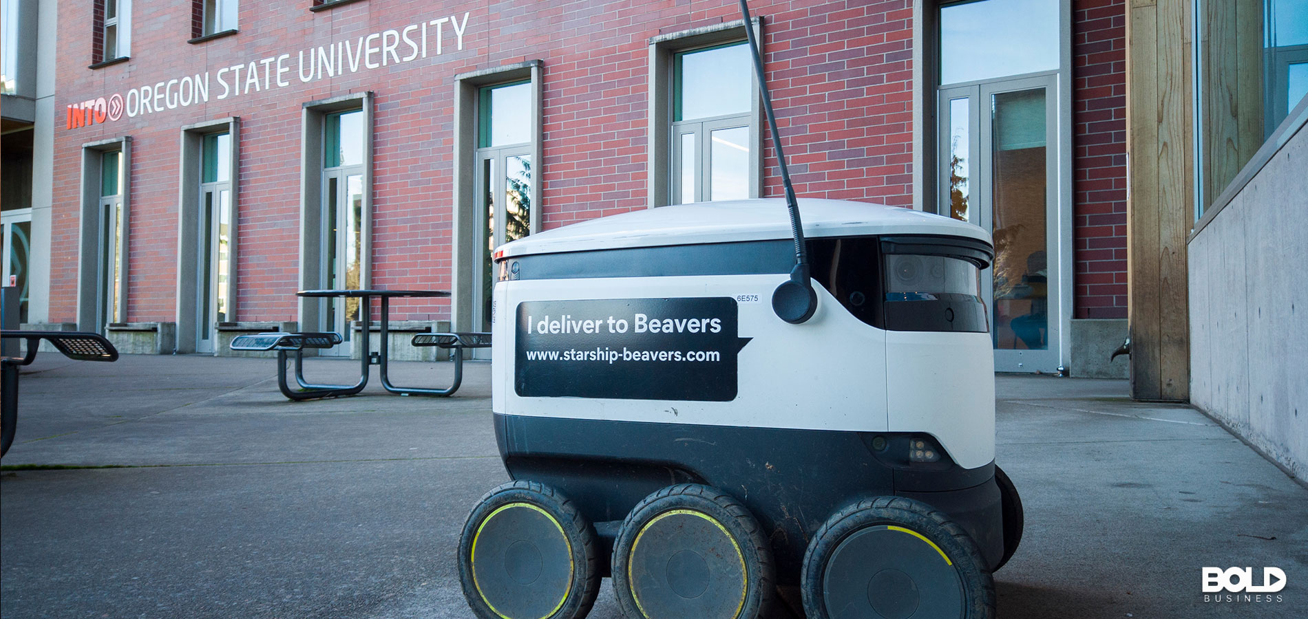 A food delivery robot delivering a pizza to some kids in the dorm