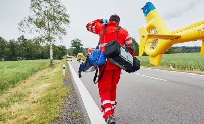 A first responder exiting a yellow helicopter